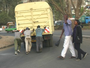 PHOTO BY JERRY SCHARF | Men push a disabled truck in Nairobi, Kenya. A common scene on Nairobi roads.
